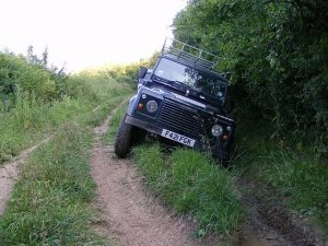 off road car stuck in rut on side of road