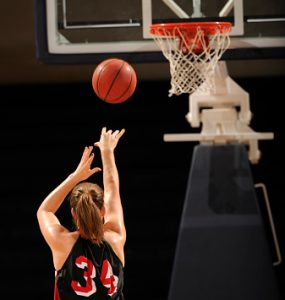 A female basketball player shoots a free throw.